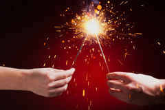 Sparklers in hands. Close-up view, red background Stock Photography