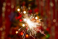 Sparklers near the Christmas tree with a red background