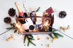 Sparklers and wooden basket with food for Christmas selebration. Happy winter holidays. Presents for Christmastime. Sparklers and wooden basket with food for royalty free stock photos