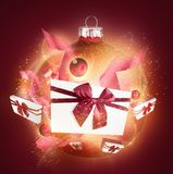 Sparkling bauble with giftboxes. Arrange of decorated presents and glowing red bauble in sparks Stock Photos