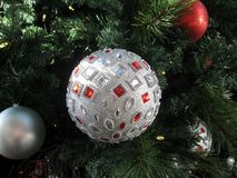 Sparkling beaded silver ball hanging on Christmas tree Stock Photos
