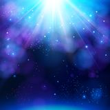 Sparkling blue festive star burst background. With a dynamic bright white explosion of rays of light over a twinkling bokeh with copyspace for your greeting or Stock Photo