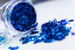 Sparkling blue glitter in a makeup jar royalty free stock photo