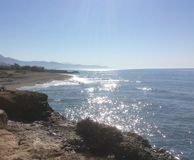 Sparkling blue sea and mountains viewed from rocky outcrop Stock Photography