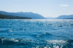 Sparkling blue water and blue mountains Lake McDonald. Glacier N Stock Image
