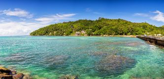 Sparkling blue water and green hill, Praslin island, Seychelles.  Royalty Free Stock Photography