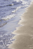 Sparkling blue water waves lapping  clean sandy beach, vertical Stock Photo