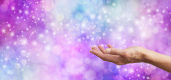 Sparkling Bokeh Glitter background and open hand. Female hand palm up in an offering gesture, on a sparkling glitter pink and blue bokeh wide background with Royalty Free Stock Photos