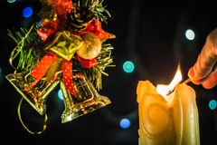 A sparkling candle lights a hand with a match. Near the branches of the Christmas tree with bells royalty free stock photo