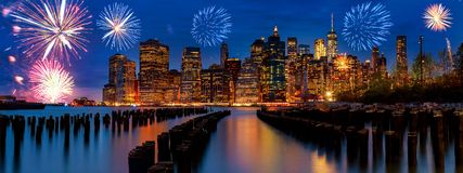 Sparkling celebration fireworks New York City Manhattan skyline with skyscrapers over Hudson River illuminated lights at dusk afte Royalty Free Stock Images