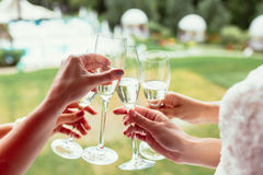 Sparkling champagne glasses in girls hands on wedding day Stock Photography