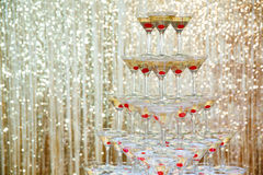 Sparkling champagne pyramid, tower of glasses at the party in front of golden wall Royalty Free Stock Images