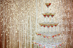 Sparkling champagne pyramid, tower of glasses at the party in front of golden wall Royalty Free Stock Photos