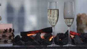 Sparkling champagne wine in glasses in front of the warm fireplace. Close up stock video footage