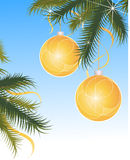 Sparkling christmas globes. Sparkling yellow christmas globes on blue background with green leaf foliage Stock Image