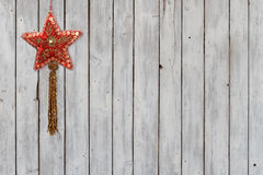 Sparkling Christmas Star Velvet Ornament on Weathered Wooden Background. Velvet sequined Christmas star ornament on white wheatered wooden background royalty free stock photo
