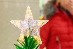 Sparkling Christmas tree toy five-pointed Russian star on top of artificial Christmas tree Stock Photos