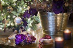 Sparkling Chritsmas decorations on wooden table. Candles, violet ribbons, petals and orchid on wooden table on background with richly decorated Christmas tree Stock Image