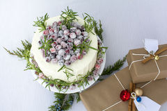 Sparkling Cranbery White Chocolate Cake with gift boxes. White chocolate cranberry cake decorated with sparkling sugar coated fresh cranberries, Holiday cake Royalty Free Stock Image