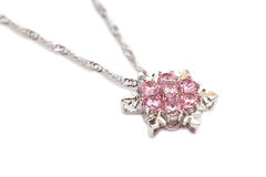 Sparkling diamond necklace. Sparkling pink diamond necklace shaped in a snow flake, isolated on white background Royalty Free Stock Photography