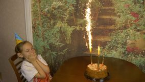 Sparkling fire fountains in a cake. Cake is on the table in front of girl. Girls Birthday. Cake with lights. Girl is. Sitting looking at the cake and afraid stock footage