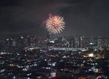 Sparkling firework bursting above Kuala Lumpur and Petaling Jaya (Malaysia). Glowing vivid sparkle of firework bursting above dark city in night. Originally stock image