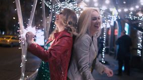 Sparkling fireworks in the hands of girls who are happy, dancing and having fun in the night city. slow motion. Best girlfriends have fun together in the night stock video footage