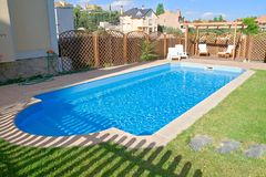 Sparkling fresh garden Pool. Brand new garden swimming pool with sparkling fresh water. Relaxing pergola with wooden garden furniture stock photo