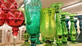 Sparkling Glass Objects in Christmas Colors. Shelved sparkling glass goblets, vases, and candlesticks in red, teal, and green Stock Photo