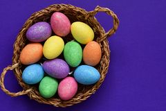 Sparkling glittering colored candy Easter eggs in a wicker basket, top view royalty free stock images