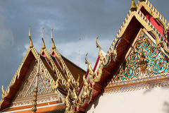 Sparkling golden roofs of buddhist temple in thunderstorm Royalty Free Stock Images