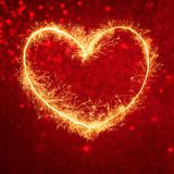 Sparkling heart on Decorative festive red background. Holiday greeting or invitation card with copy space for design  for the Valentine`s Day, wedding, mother` Stock Photo