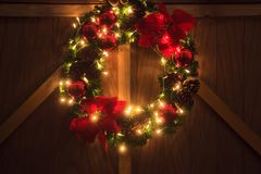 Sparkling Illuminated Christmas Garland Wreath at night of Christmas Eve. Christmas decoration with blinking warm golden. Incandescent light on wooden wall royalty free stock photos