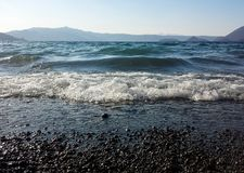 Sparkling lake waves mountain on background stock images