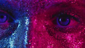 Sparkling makeup woman blue eyes glitter face skin. Sparkling makeup. Glamour vision. Woman with blue eyes and glitter face skin in neon pink glow stock footage
