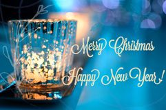 Merry Christmas Happy New Year Card. Merry Christmas and Happy New Year Vintage Card with sparkling candle burning flame in blue background card with copy space Royalty Free Stock Photos