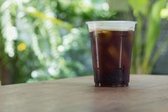 Sparkling Nitro Cold Brew Coffee in take away cup. Sparkling Nitro Cold Brew Coffee ready to drink.Outdoor cafe in tropical design Royalty Free Stock Images