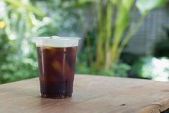 Sparkling Nitro Cold Brew Coffee in take away cup. Sparkling Nitro Cold Brew Coffee ready to drink.Outdoor cafe in tropical design Stock Photo