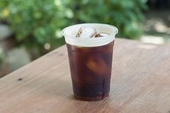 Sparkling Nitro Cold Brew Coffee in take away cup. Sparkling Nitro Cold Brew Coffee ready to drink.Outdoor cafe in tropical design Royalty Free Stock Image