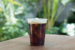 Sparkling Nitro Cold Brew Coffee in take away cup. Sparkling Nitro Cold Brew Coffee ready to drink.Outdoor cafe in tropical design Stock Image