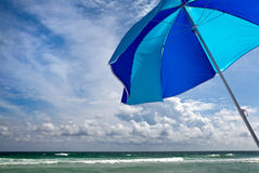 Sparkling Ocean with Beach Umbrella. Blue and aqua beach umbrella blowing in the wind on a bright sunny day at the seaside Royalty Free Stock Photo