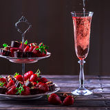 Sparkling pink wine is poured in glass. Stand with strawberries. And sweets on a wooden table. Delicious dessert. Atmosphere of luxury and a romantic evening stock photo