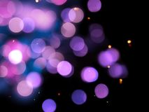 Sparkling purple round blurred lights on a black background royalty free stock images