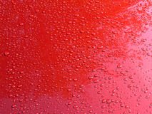 Sparkling rain drops on a shiny red car body after a brief shower. Stock Image