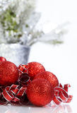 Sparkling Red Christmas Ornaments. And curly ribbons on reflective white surface Stock Photography