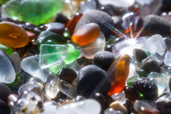 Sparkling sea glass. Close up of a group of shiny pieces of sea glass on the beach using a star filter to obtain a sparkling effect Royalty Free Stock Image