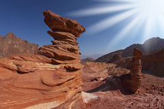 The sparkling sun above forms of sandstone Stock Image