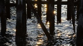 Sparkling sunshine reflection on fjord waves under wooden pier. Background video stock video footage