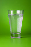Sparkling Water. A glass of sparkling mineral water on green background Royalty Free Stock Image