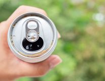 Sparkling water in can. Opened can with sparkling water in hand on green nature background with copy space Royalty Free Stock Image